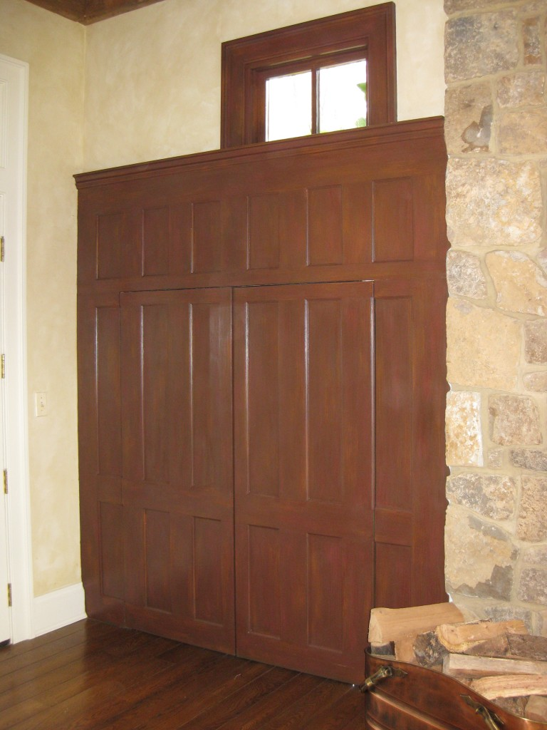 Paneled wood cabinetry and windows painted to replicate dark mahogany wood finish.