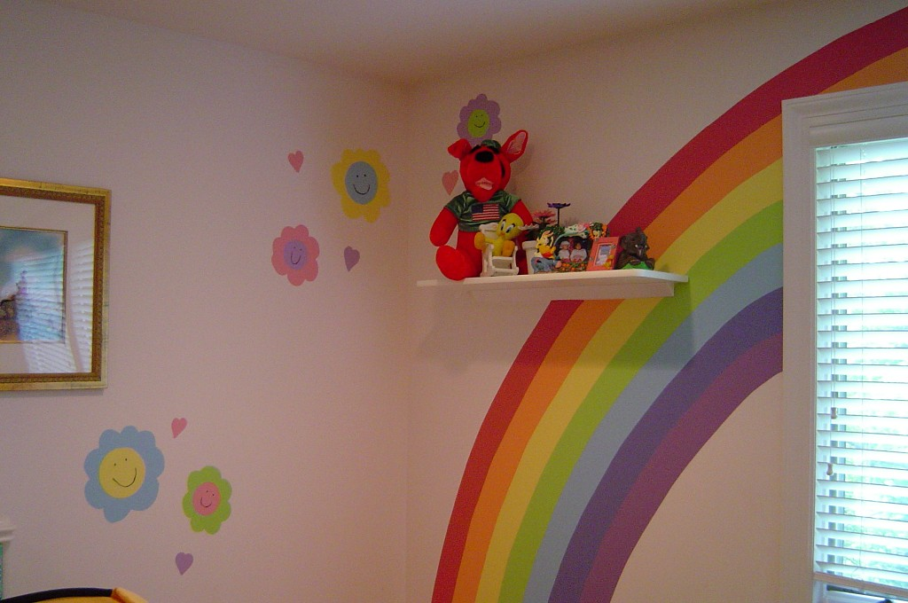 rainbow and happy flowers painted in a playroom.