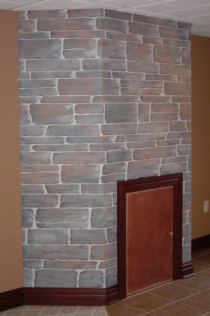 False fireplace accent wall painted to replicate actual stone fireplace wall elsewhere in the home.