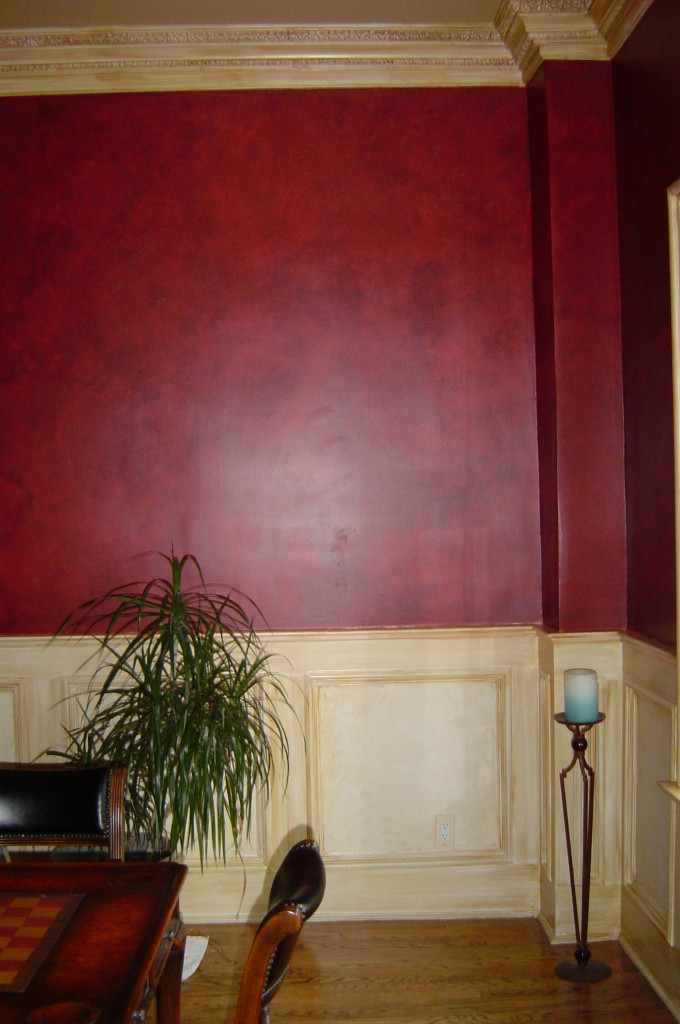 """Dining room walls are glazed in a warm black over red to resemble leather. All trim is """"antiqued"""" with a sepia glaze."""