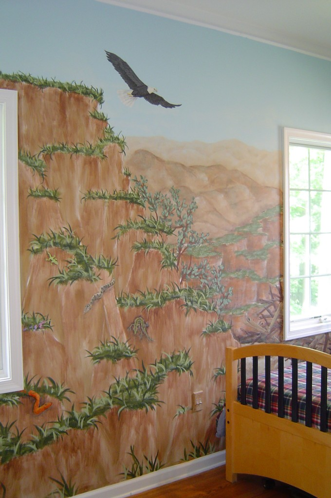 Rocky landscape mural with eagles painted in boy's bedroom.