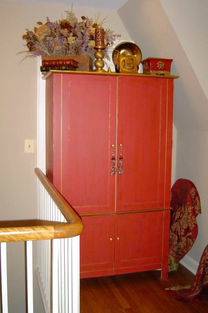 Maple computer armoire painted in a rustic red with dry-brushed glaze and gold accents.