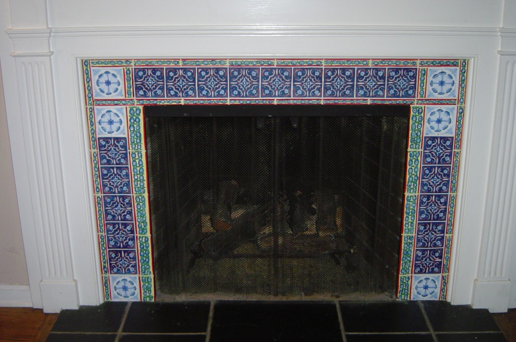 Faux decorative tile painted on slate fireplace surround.