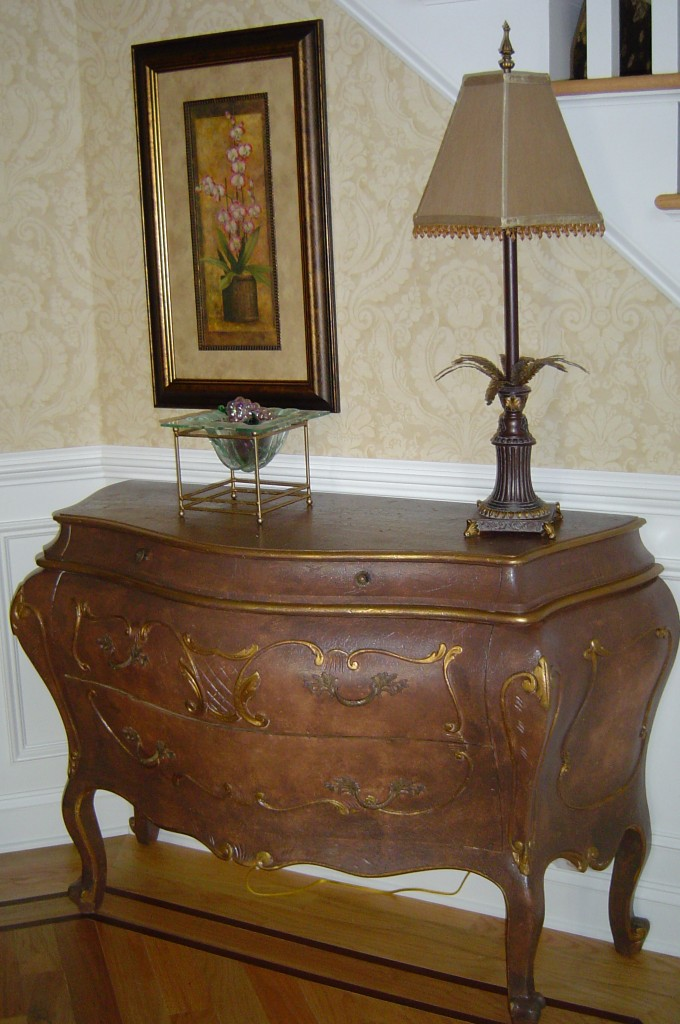 Bombe chest painted with brown glaze and gold accents.