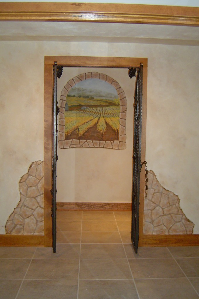 Wine Cellar painted with textured plaster, break-away stone effect, aged color wash, and faux window with Tuscan vineyard mural.