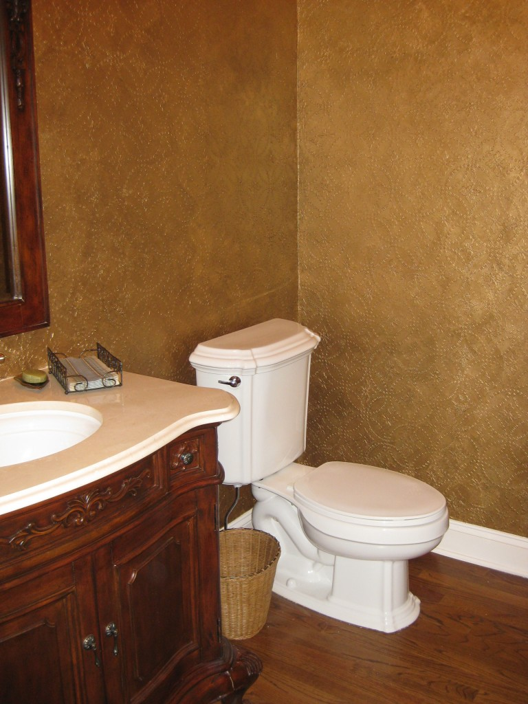 Dimensional plaster stencil design applied in powder room, then painted with an antique metallic gold finish.