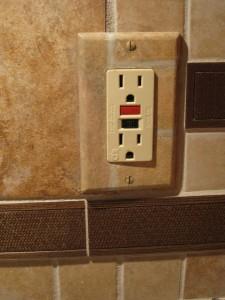 Outlet plate painted to blend into backsplash tile pattern.