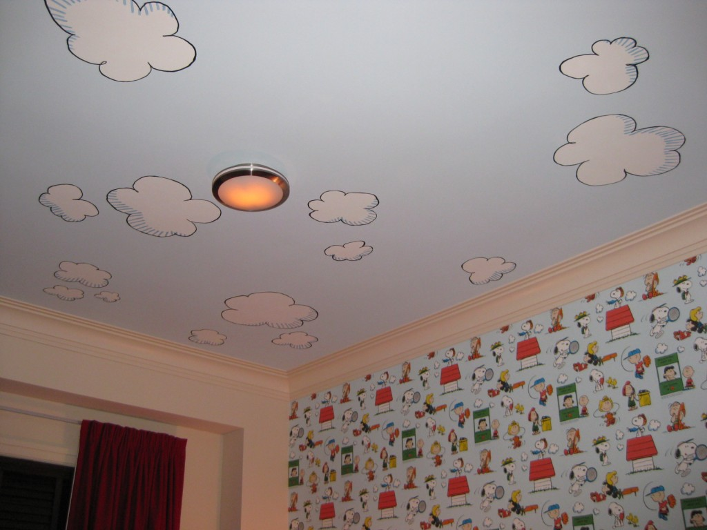 "Cartoon clouds painted on ceiling to complement the vintage ""Peanuts"" wallpaper."