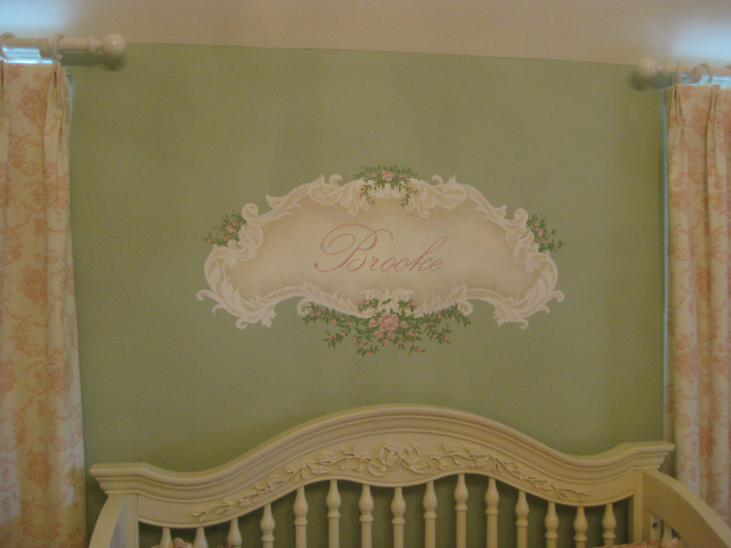 Decorative cartouche with baby's name painted above nursery crib.