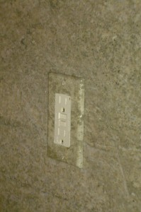 Outlet plates and switch covers painted to blend into the green granite backsplash.