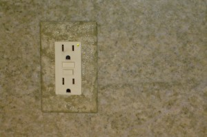 Outlet plates painted to blend into the granite backsplash.