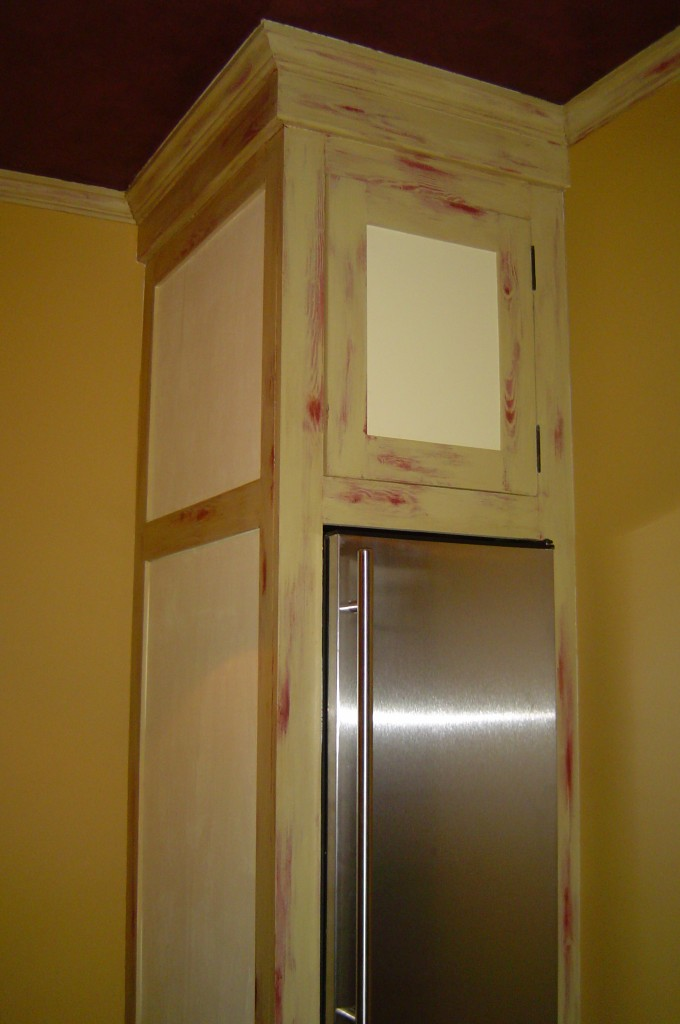 Pantry cabinetry painted with pale yellow-green and rubbed through to reveal red undercoat and oak wood grain relief.