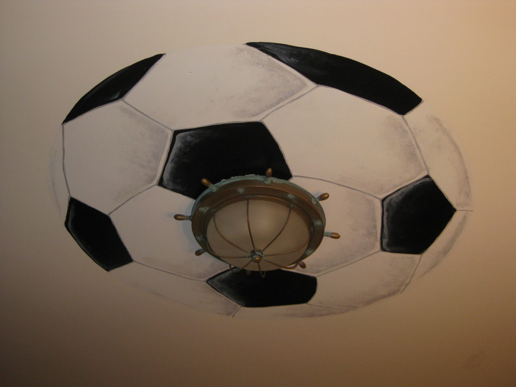 Giant soccer ball painted around light fixture.