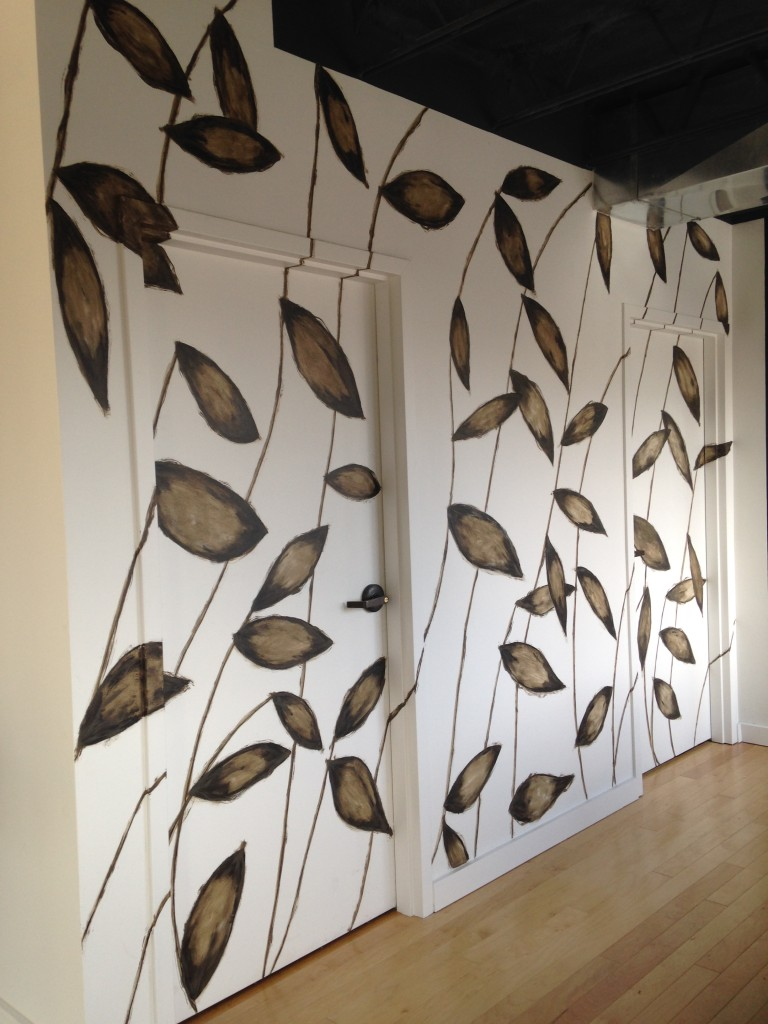 Large graphic leaf design camouflages the doors in this hallway.