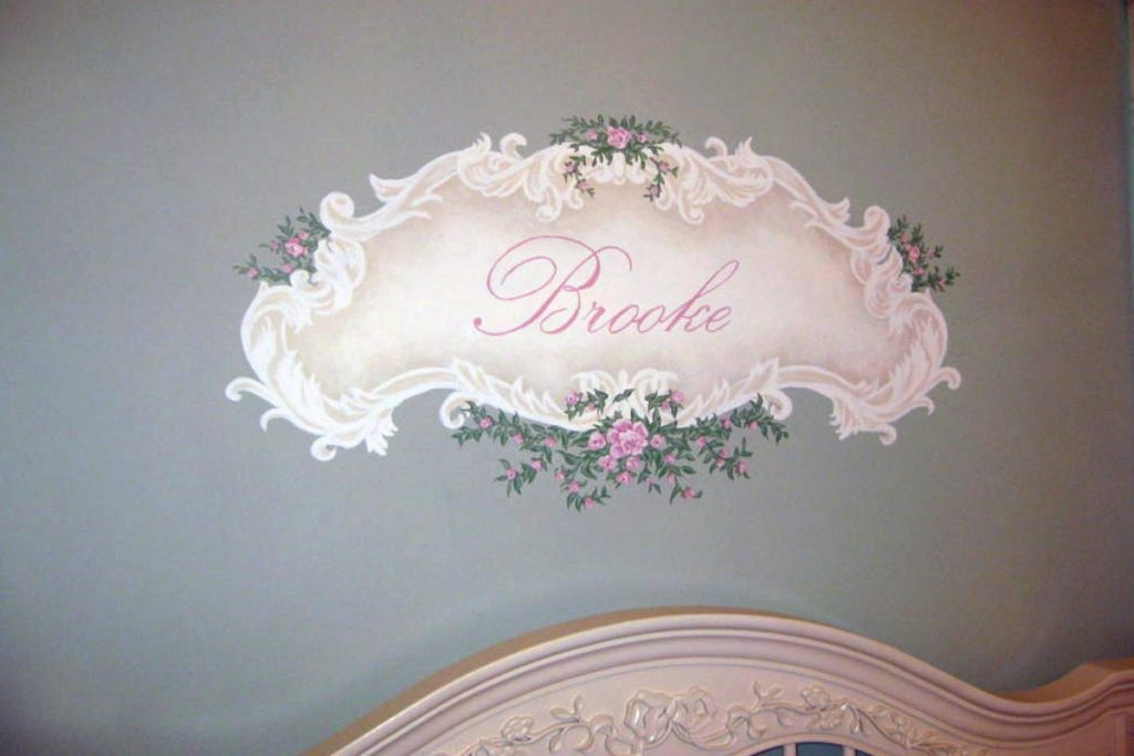 For the nursery, the baby's name painted in a faux carved frame with flowers.