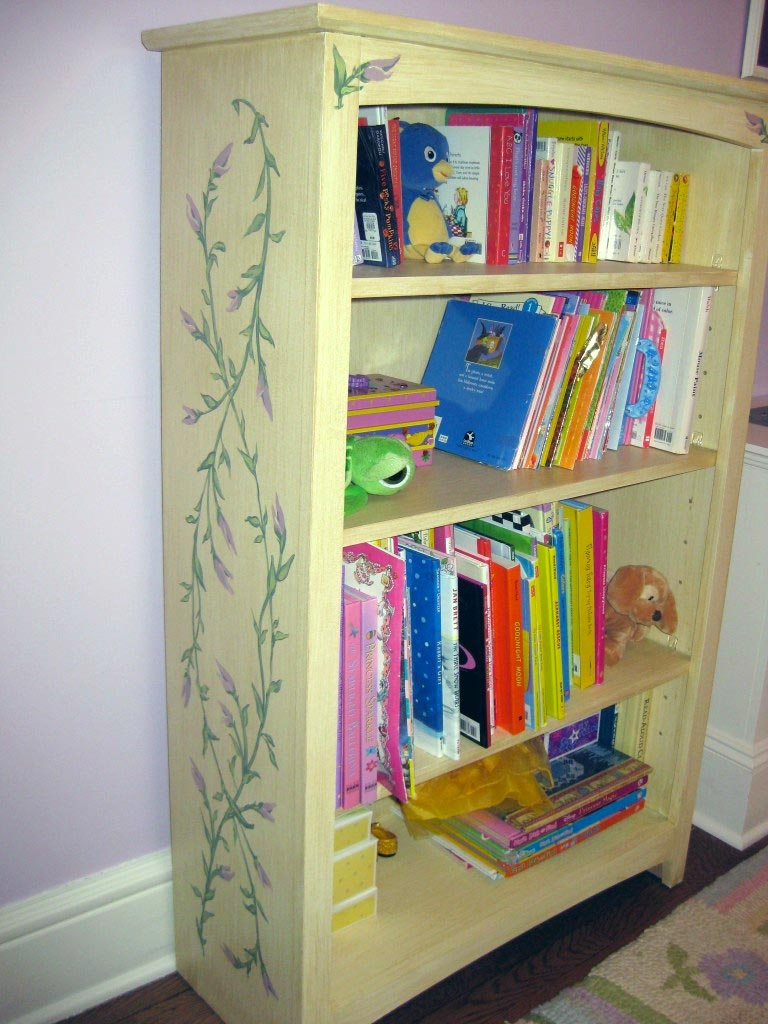 Unfinished bookcase painted with antique glaze and decorative floral designs.