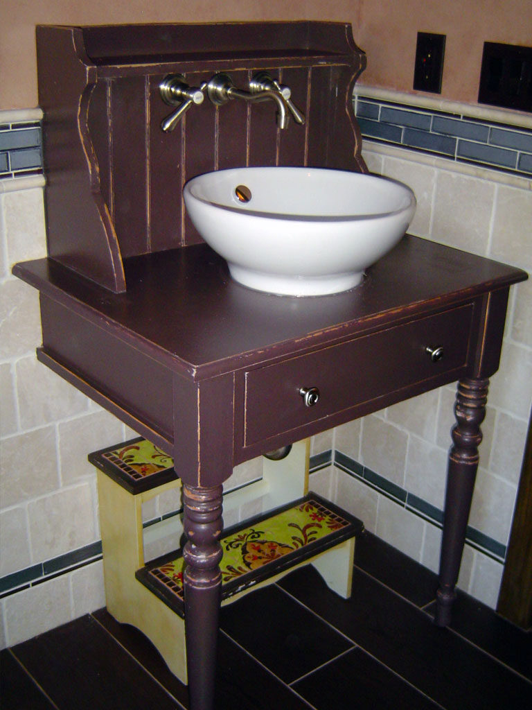 Bathroom vanity painted chocolate brown and rubbed through to reveal bare wood along the edges.