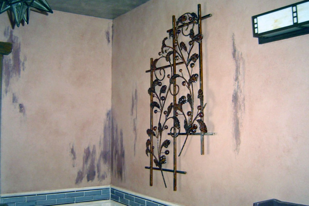 Bathroom walls painted in multi-layer worn-away finish with glaze overall.