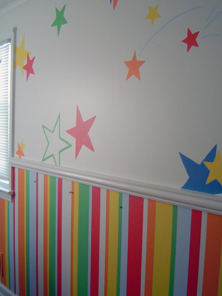 Children's bedroom painted with bright multi-colored stripes and stars.