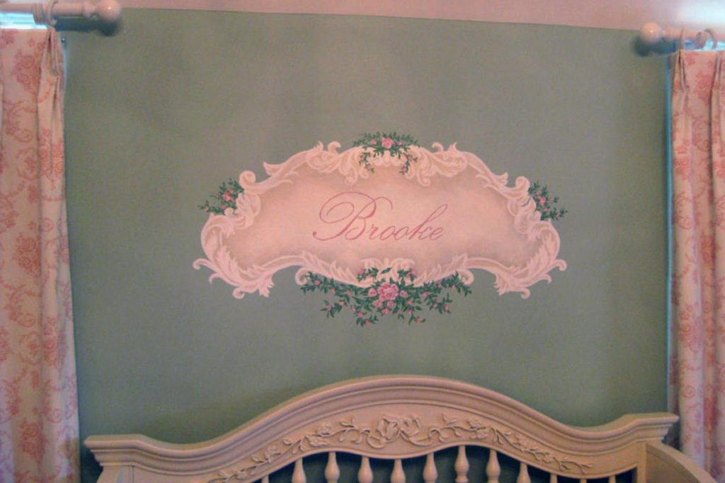 Decorative cartouche painted above nursery crib.