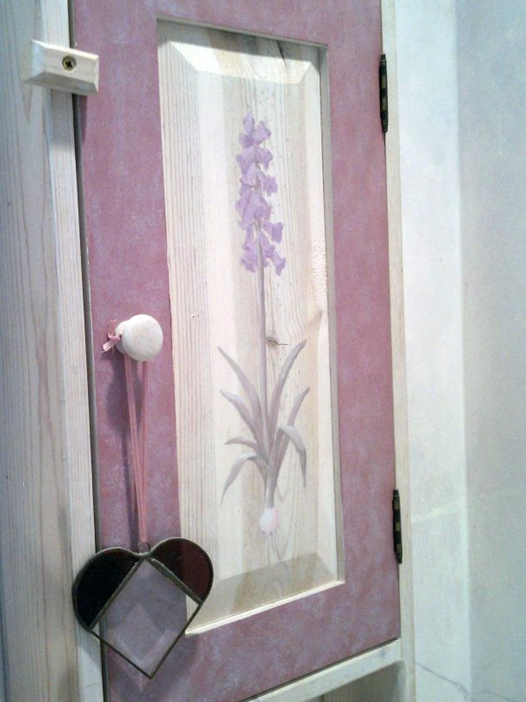 Decorative floral design painted on cabinet.