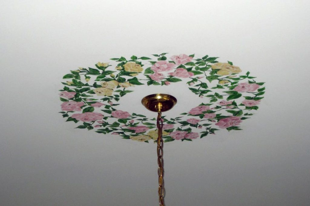 Decorative floral design painted around chandelier base.