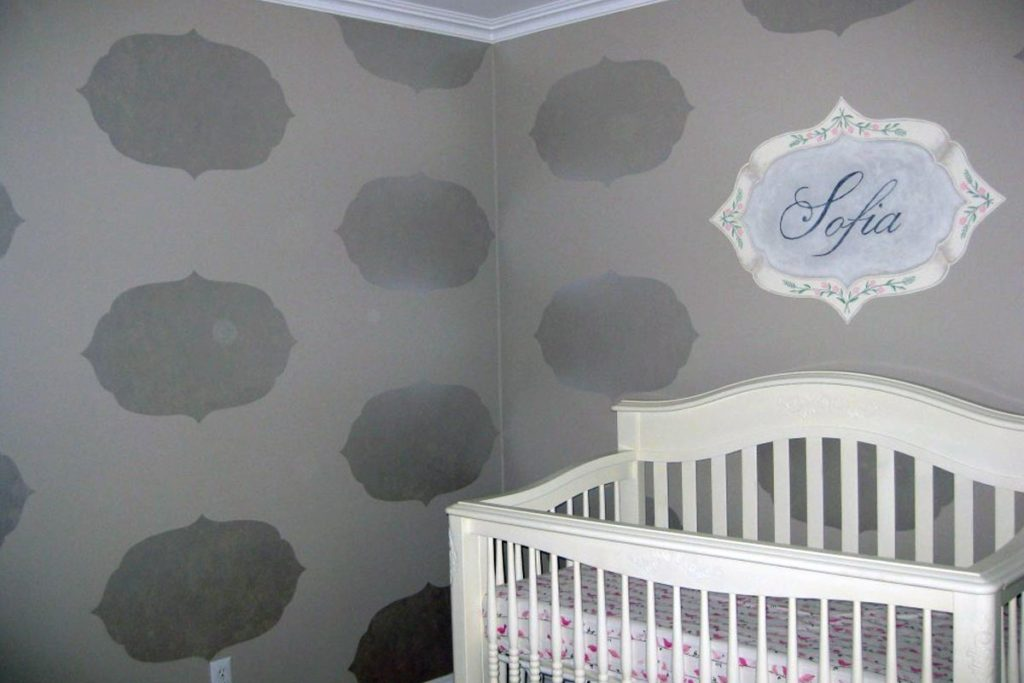 Decorative name plaque and iridescent silhouette of frame shape painted around the room.