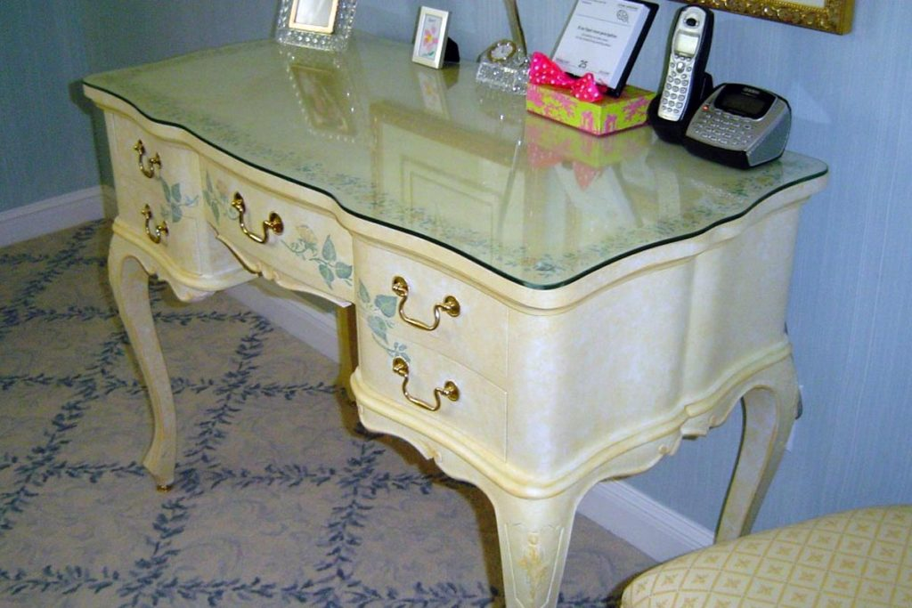 Dressing table painted with soft yellow glaze overall and floral details painted on top and sides.