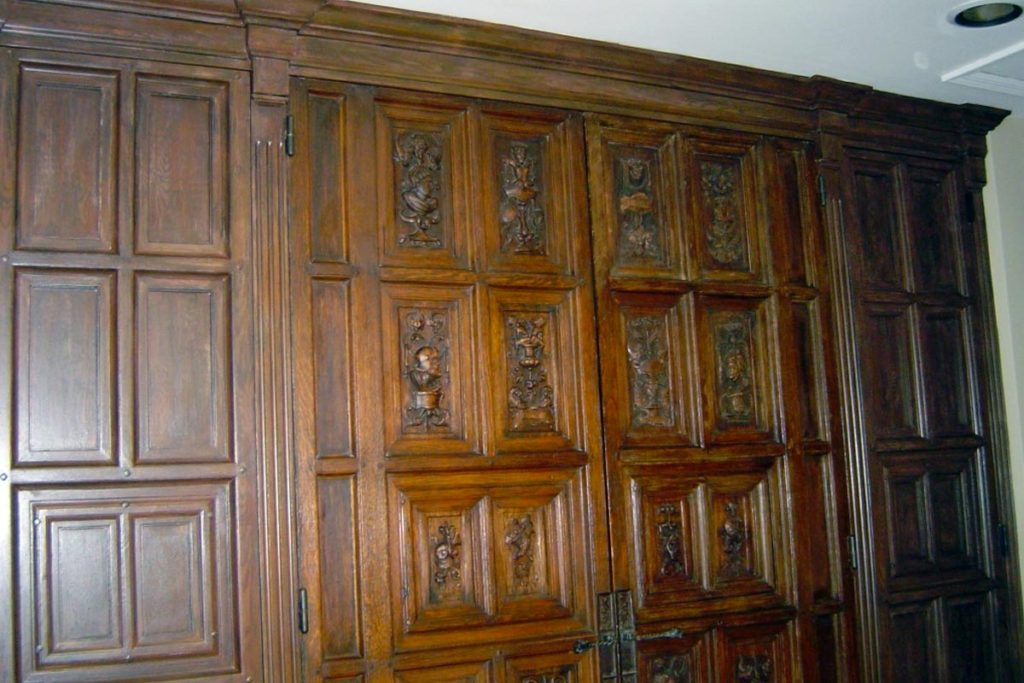 Newly constructed architectural trim and door panels painted with a faux wood-grain to replicate the antique carved door panels in the center.