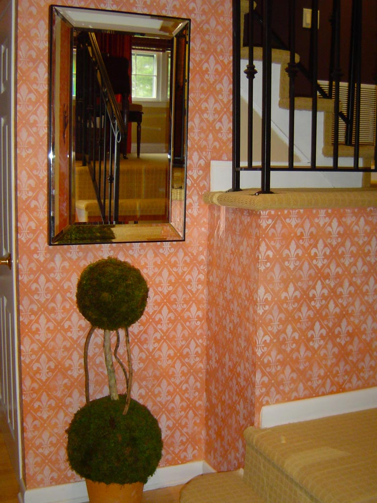 Translucent fleur-de-lis stencil painted over washed terracotta blended basecoat in foyer.