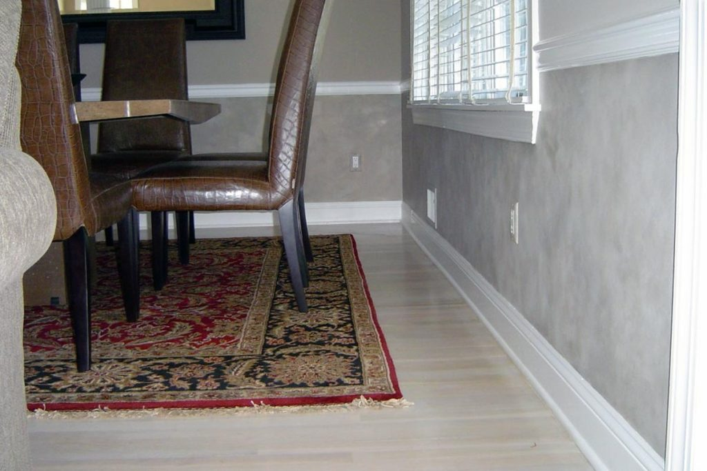 Washed grey stone finish below chair rail in dining room.
