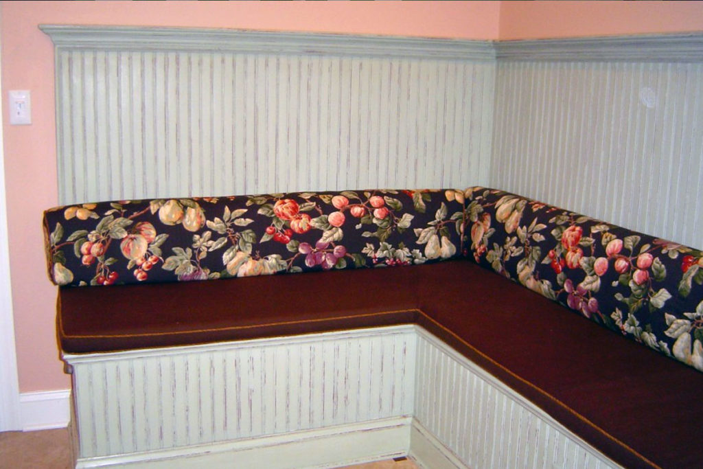 Kitchen banquette painted with soft green and distressed to reveal copper base color.