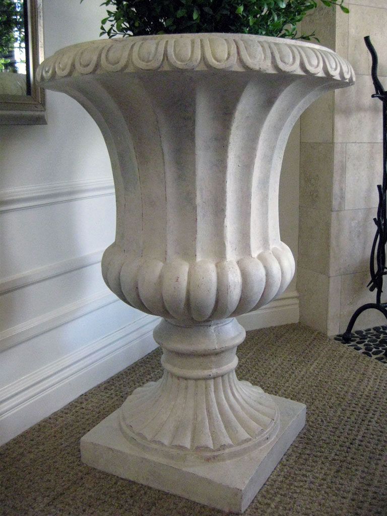 Black fiberglass planter painted to resemble aged stone.