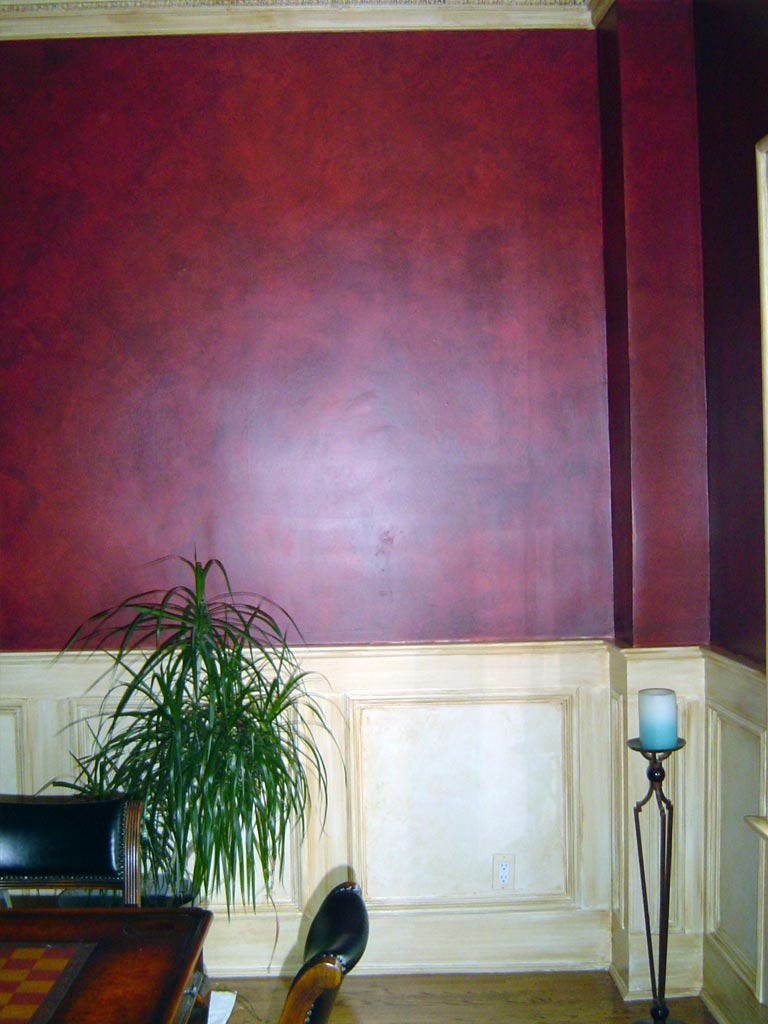 "Dining room walls are glazed in a warm black over red to resemble leather. All trim is ""antiqued"" with a sepia glaze."