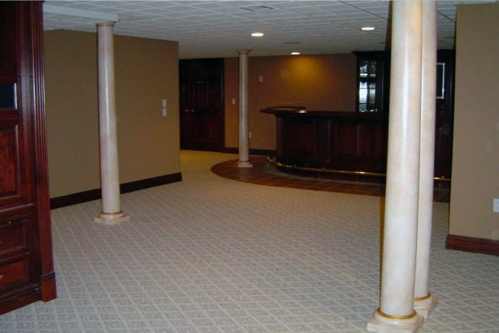 Basement support columns painted to resemble polished stone with gold accents.