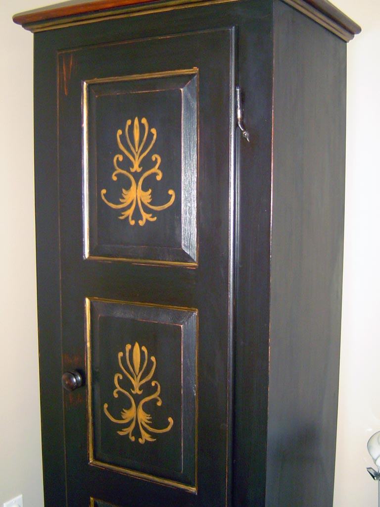 Storage cabinet painted with custom stenciled and hand-painted gold details.
