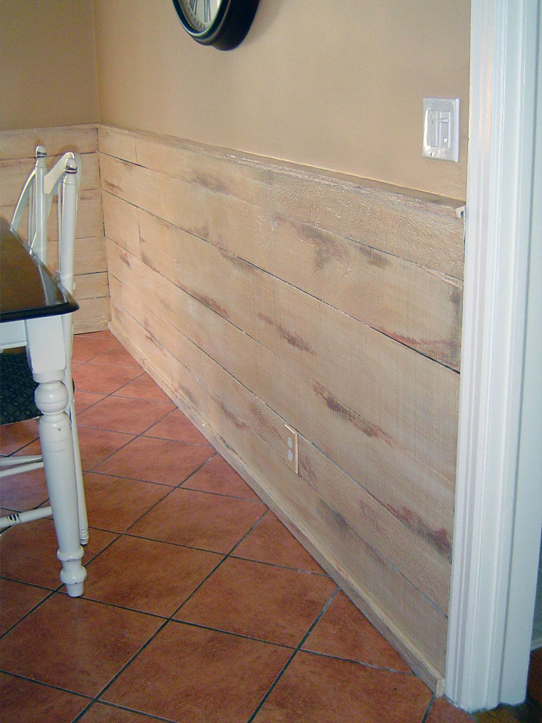 Barn-board wainscot painted with distressed technique to reveal multiple layers of paint.