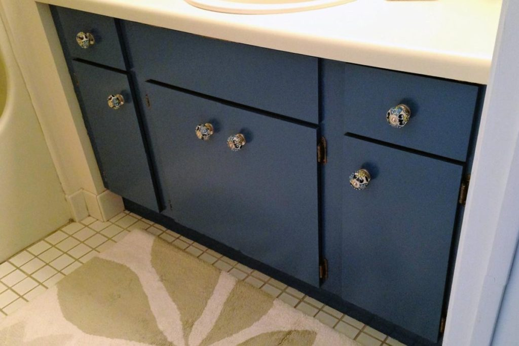After: Properly sanded, primed, and painted a bright teal color, this vanity cabinet looks fresh and updated, with new decorative knobs adding the finishing touch!