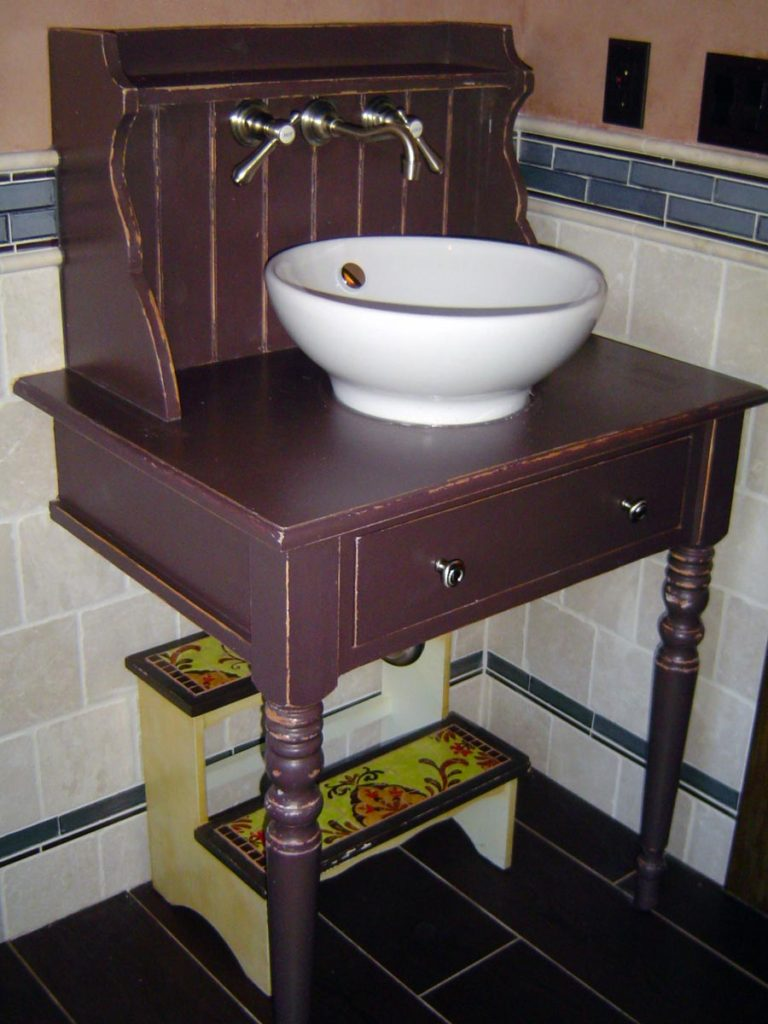 Originally a small desk, this piece was cut apart, rebuilt, and fitted with a sink and plumbing, then painted chocolate brown and rubbed through to reveal bare wood along the edges.