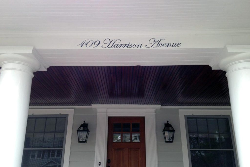 A hand-painted address, on the header of the front porch.
