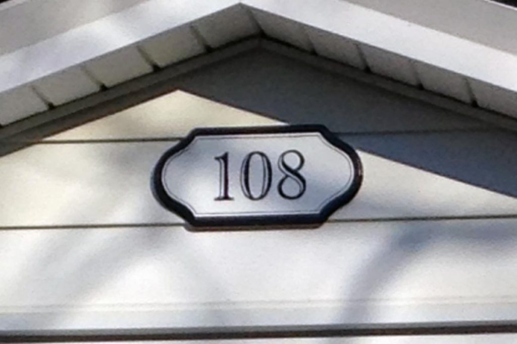 Home address in custom-selected font painted along with simple border, on an decorative wood plaque.