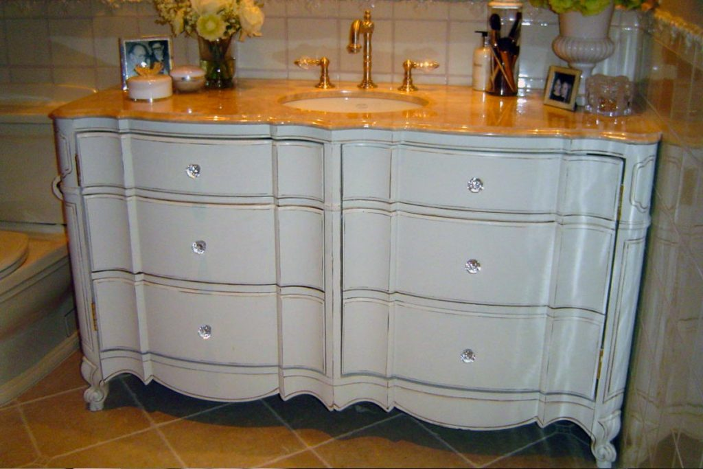This master bathroom vanity was once a bedroom dresser. Repainted, antiqued and finished in gloss polyurethane, new hardware, and a granite counter top surface and sink replaced the furniture top.