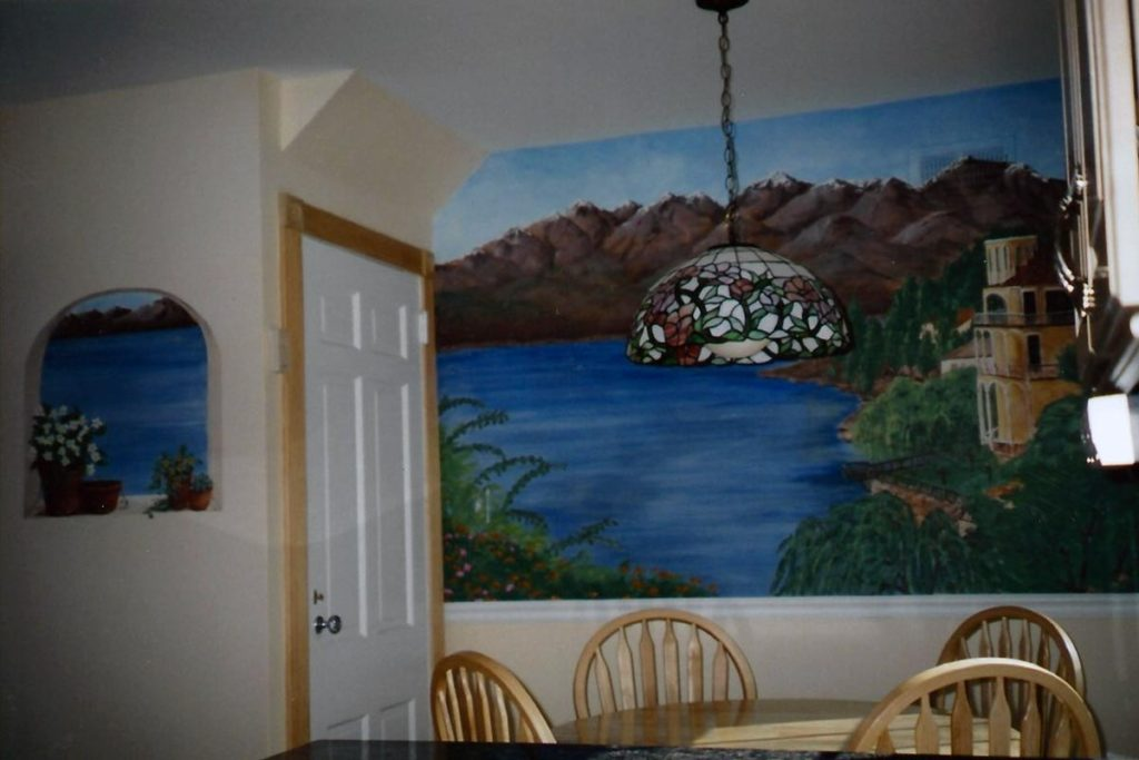 Here is a mural in a kitchen dining area, including a small painted faux window with the same view. Mural of Italian lakeside scene with additional view from faux window.