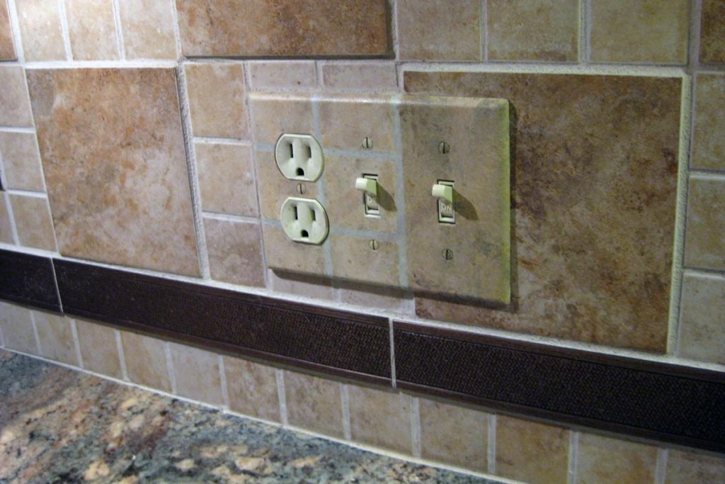 Switch/outlet plate painted to blend into backsplash tile pattern.