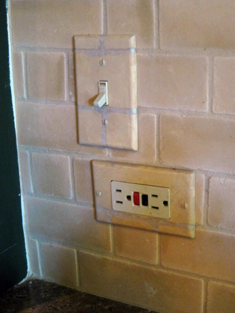Particularly when the switch and outlet placement is unusual on the wall, it helps to paint everything for a uniform look. Switch and outlet plate painted to match brick backsplash tile.