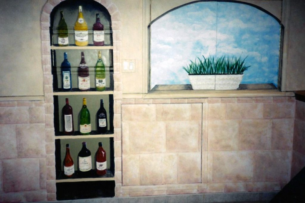 This mural had a few challenges, as the basement wall was broken up by a series of utility access panels. One became the window, one is part of the stone wall, and a third…. Wine cabinet and window painted on a background of stone wall. Wine cabinet and window painted on a background of stone wall.
