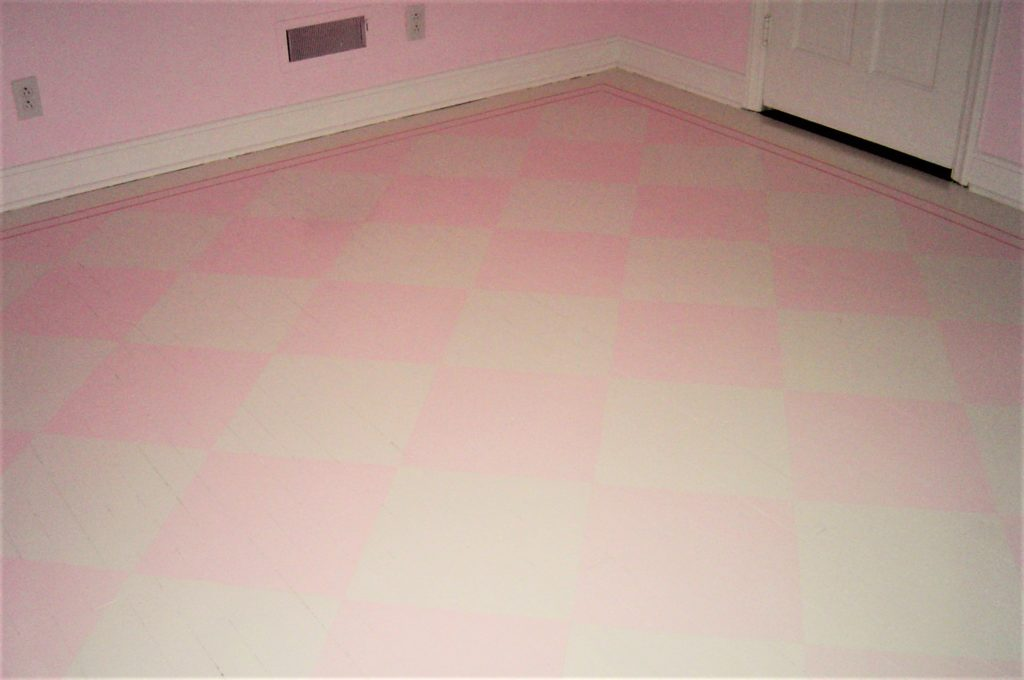 Hand painted pink and white grid pattern on hardwood floor.