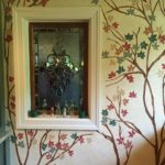 Hand painted branches and flowers over glaze finish in kitchen of historic home.