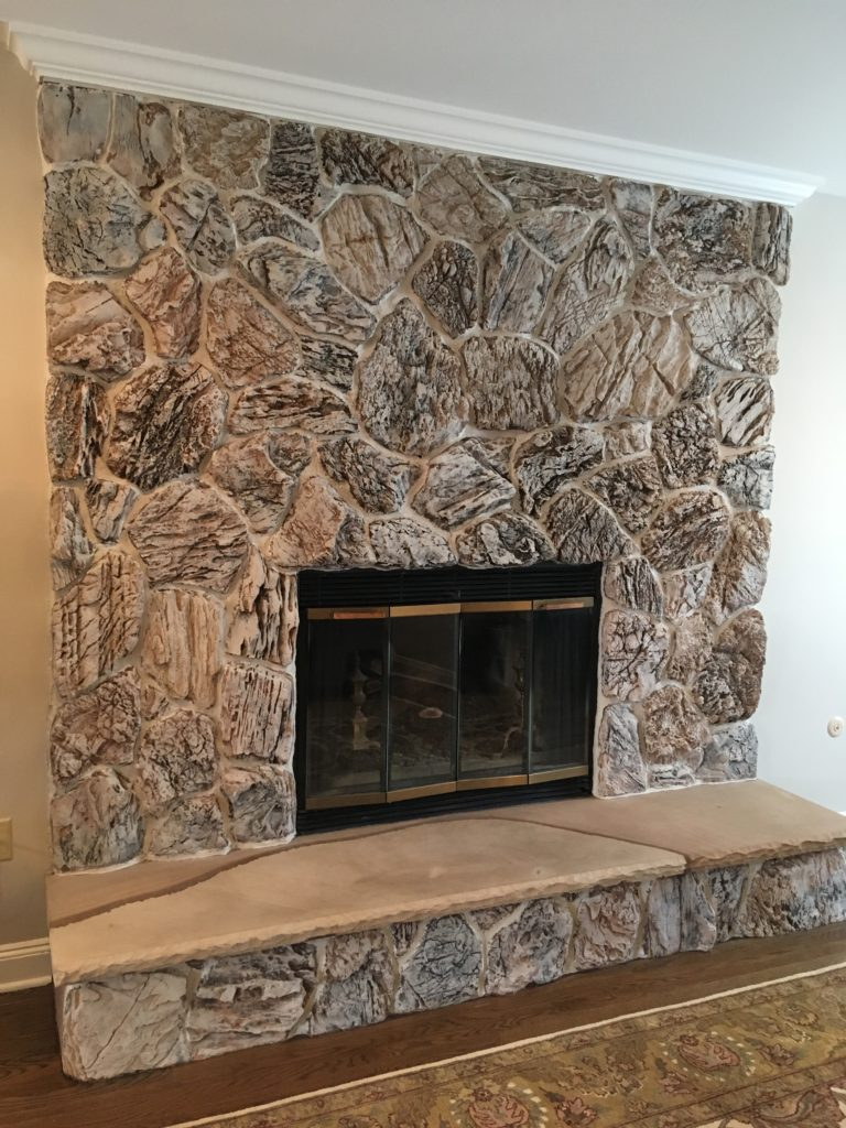 Fireplace painted with light grey mortar and color wash over the stones.