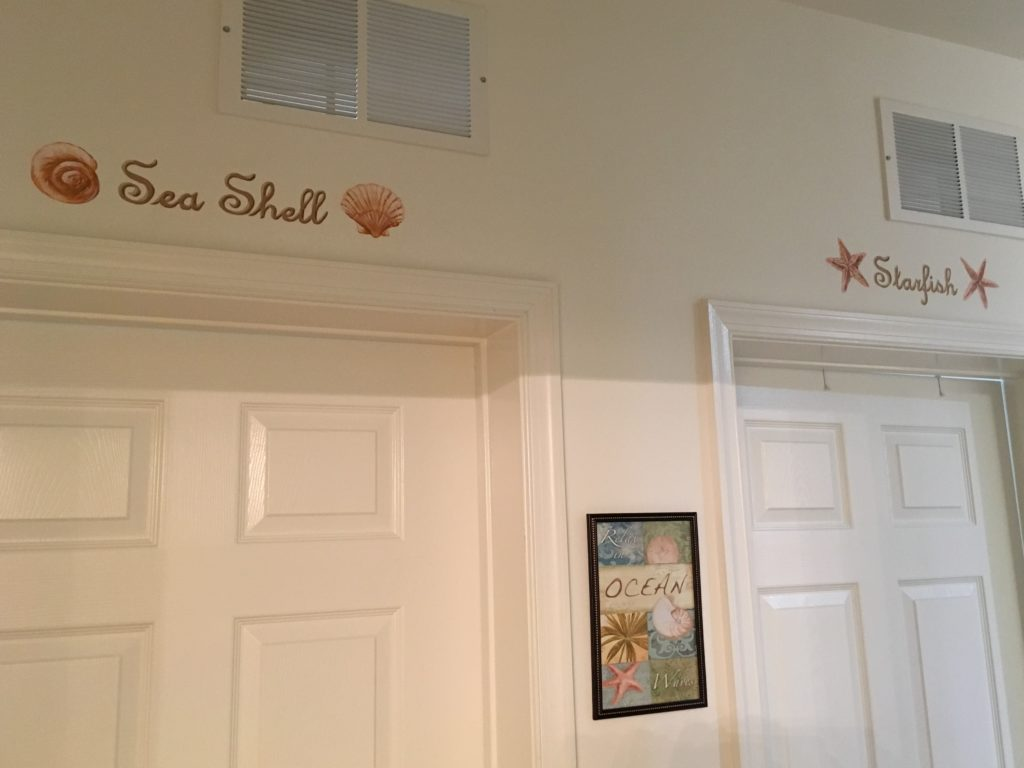 Hand painted signs above bedroom doors in beach house.